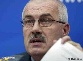 The Belarus Interior Minister Vladimir Naumov is seen holding documents at a press conference.
