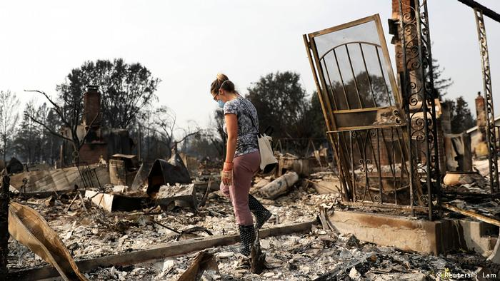 A woman surveys her home that was destroyed by the fire
