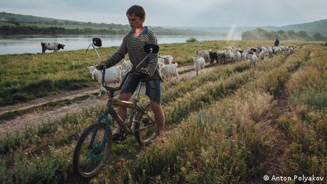 Boy riding a bike through a field