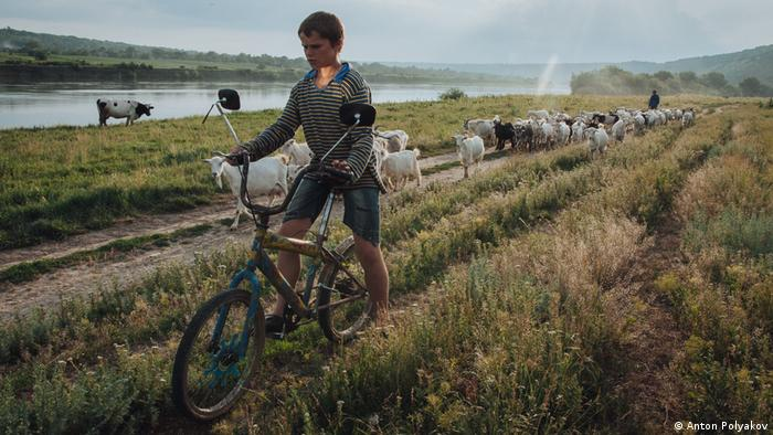 Boy riding a bike through a field