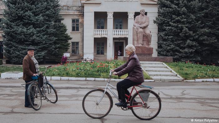 woman riding a bike past a statue of Lenin