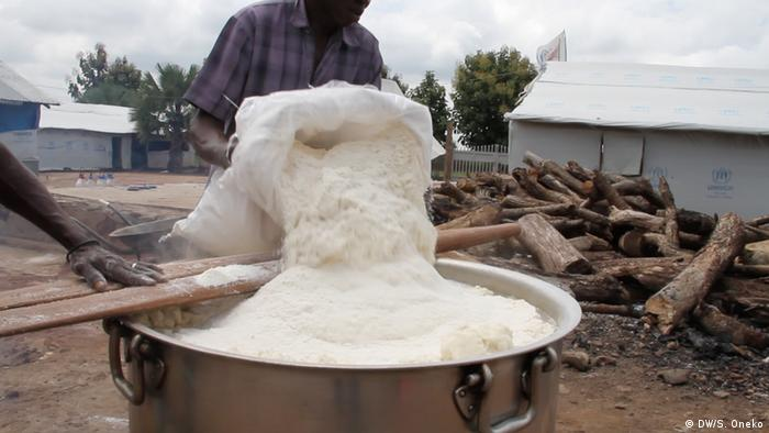 Corn flour is being poured from a big white sack into a very large metal pot.