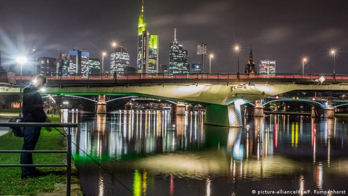 A fisherman stands near the Main River in Frankfurt at night