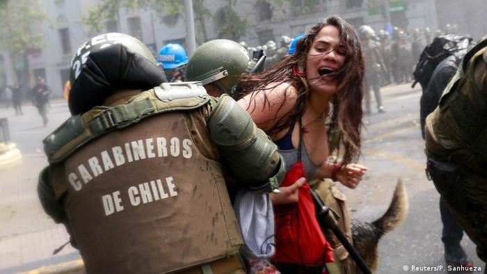 A demonstrator is detained by riot police during a rally against Columbus Day in downtown Santiago, Chile