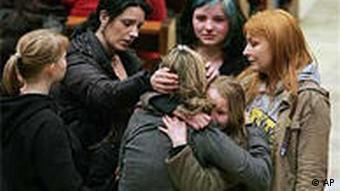 Teary-eyed people embracing outside the school in Winnenden