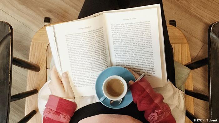 A person reads a book with a coffee in her hand (DW/K. Schenk)