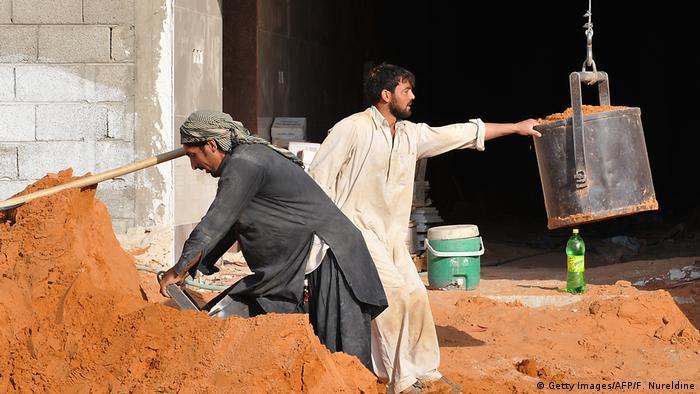 Two men work shovelling soil on a construction site