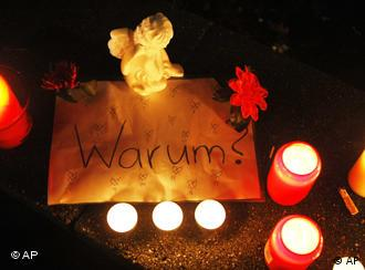 Candles burn around a sign with the word 'warum', or 'why', written on it