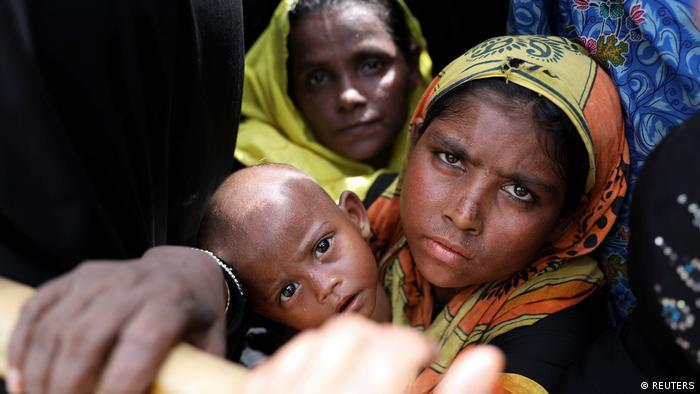 Rohingya refugees wait for food to be distributed