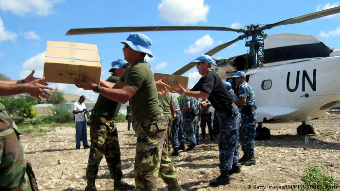 Haiti MINUSTAH workers unload aid packages from a helicopter