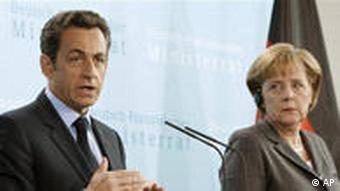 German Chancellor Angela Merkel, right, and the President of France, Nicolas Sarkozy, left, address the media after a meeting of the German and French governments in Berlin