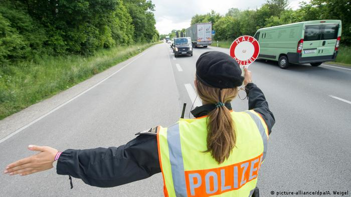 A police officer waves at vehicles to stop at a checkpoint near Germany's border with Austria
