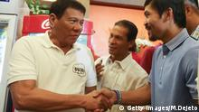 Philippines' President-elect Rodrigo Duterte (L) shakes hands with boxing icon and newly elected Senator Manny Pacquiao at a meeting in Davao in southern island of Mindanao on May 28, 2017. Philippine police shot dead four suspected drug dealers while unknown men gunned down two others, officials said Saturday, raising the death toll for narcotics suspects to 14 this week after president-elect Rodrigo Duterte vowed a war against crime. / AFP / MANMAN DEJETO (Photo credit should read MANMAN DEJETO/AFP/Getty Images)