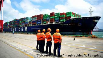 Рабочие перед контейнерным судном в китайском порту
