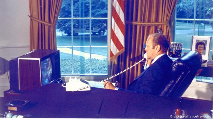 In the Oval Office, US President Gerald Ford watches Apollo-Soyuz crewmen on a screen while talking to them on the phone in 1975