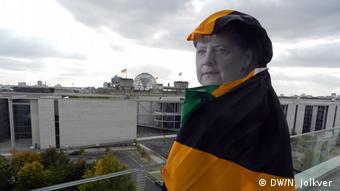 Какой-то шутник в парламентской редакции DW закутал картонную Меркель во флаг Ямайки