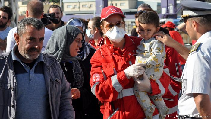 Red Cross worker carrying child (Getty Images/AFP/A. Fucarini)