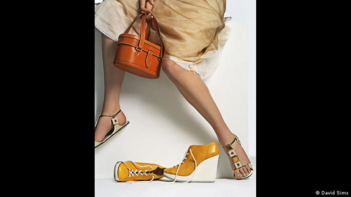 A photo of a model holding shoes and a purse in the Jil Sander show in Frankfurt (David Sims)