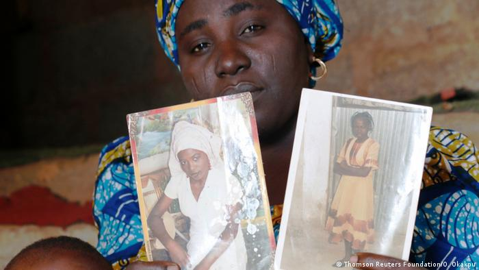 A woman in Nigeria holds two photographs of her daughter who were kidnapped by Boko Haram