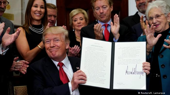 Trump smirks as he holds up a folder with plans for a bare-bones insurance offerings