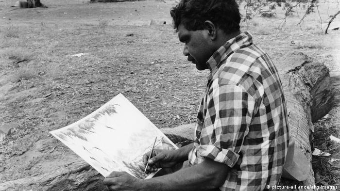 Albert Namatjira painting the Australian countryside while sitting on a log.