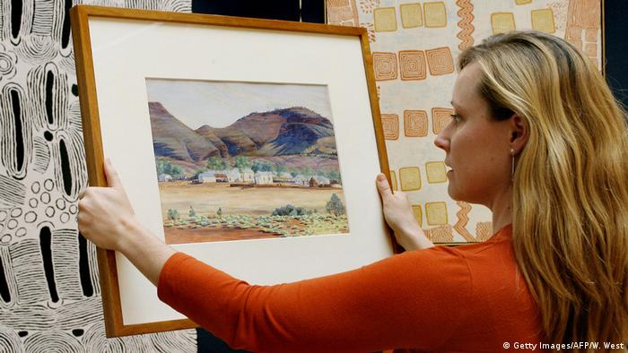 A woman holding a painting by Albert Namatjira (Getty Images/AFP/W. West)