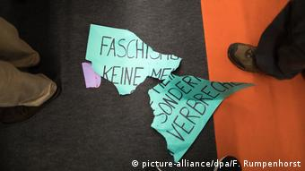 A torn sign on the ground reads fascism is not an opinion