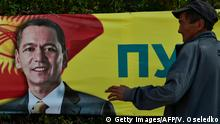 12.10.2017 +++ A man stands in front of an election campaign banner of Kyrgyz opposition MP and presidential candidate Omurbek Babanov in the village of Kara-Jigach, 20 km of Bishkek, on October 12, 2017. Kyrgyzs will go to the polls for the presidential election on October 15, 2017. / AFP PHOTO / Vyacheslav OSELEDKO (Photo credit should read VYACHESLAV OSELEDKO/AFP/Getty Images)