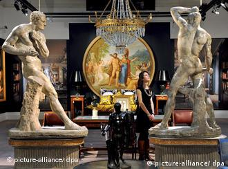 A woman gazes up at a statue that makes up the collection of Versace items to be auctioned off by Sotheby's