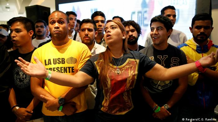 Opposition supporters react while listening to the results of the nationwide election for new governors, at the campaign headquarters of the Venezuelan coalition of opposition parties (MUD) in Caracas,