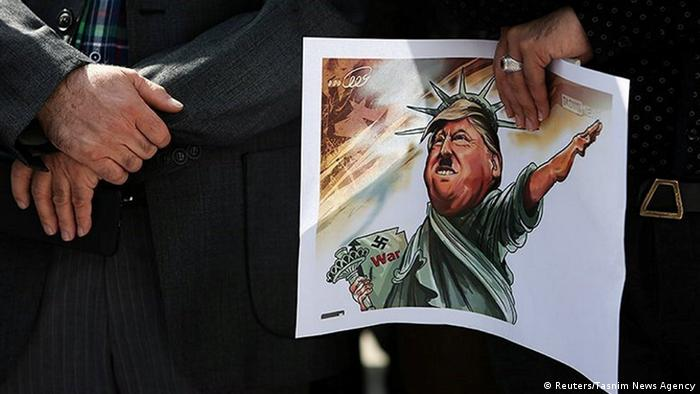 A person in Tehran holding a cartoon portraying Trump as a Nazi