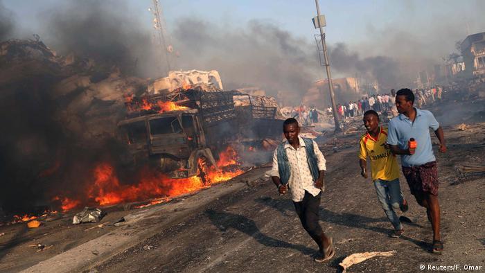 Civis evacuam a rua KM4 em Mogadíscio após caminhão-bomba explodir e deixar 300 mortos