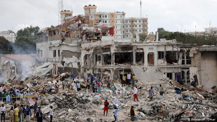 People walk amid the rubble of a bombed building