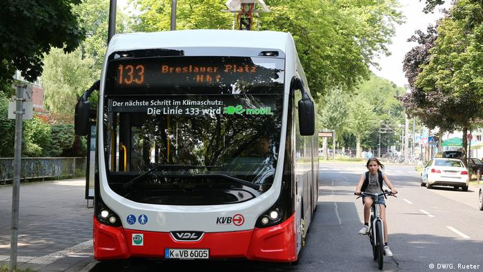 An E-bus and a cyclist cruise along Cologne's city streets | Elektrobus mit Batterie (DW/G. Rueter)
