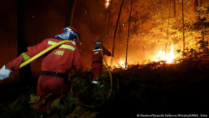 Firefighters from the Military Emergency Unit (UME) work to put out a forest fire near As Nieves, northern Spain
