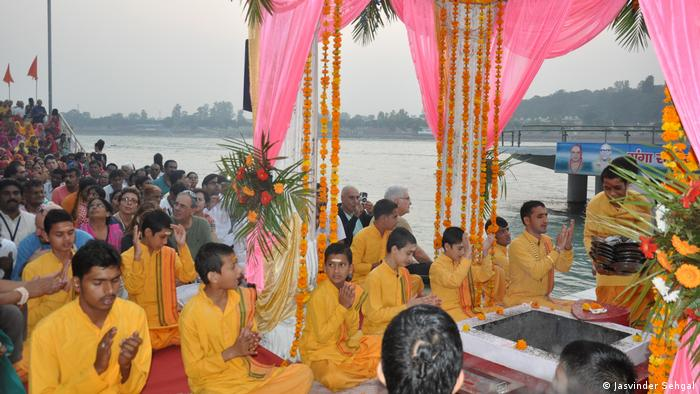 Worshippers dressed in yellow, by the river
