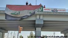 KIRKUK, IRAQ - OCTOBER 16: People cover the boards hang by Iraqi Kurdish Regional Government (IKRG) for Illegitimate independence referendum with Iraqi flag as Iraqi Army members conduct inspection on highways with armored vehicles following peshmergas of Patriotic Union of Kurdistan (PUK) withdraw from southern part of Kirkuk in Iraq on October 16, 2017. Hassan Ghaedi / Anadolu Agency |
