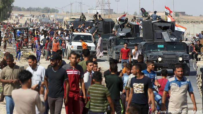 Iraqi civilians gather as Iraqi forces arrive in the first neighbourhood on the southern outskirts of Kirkuk