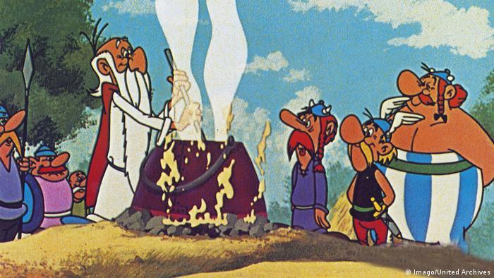 Asterix und Obelix sowie ein als Gallier verkleideter Römer schauen Miraculix beim Brauen des Zaubertranks zu