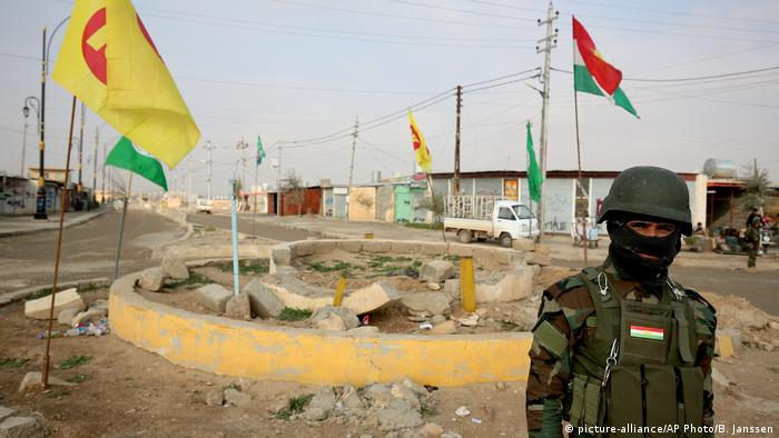 A KDP peshmerga fighter stands at a destroyed roundabout in a town near Sinjar, northern Iraq
