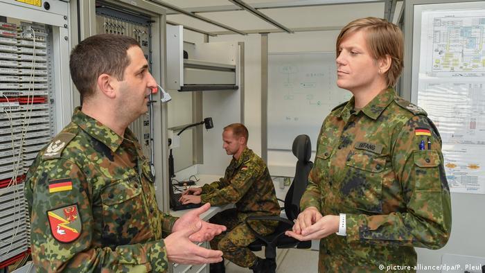 Dois militares em roupas camufladas conversam numa sala, com outro militar sentado ao computador ao fundo