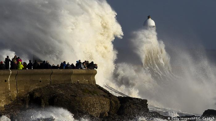 Huge waves strike the harbor wall and lighthouse at Porthcawl, south Wales