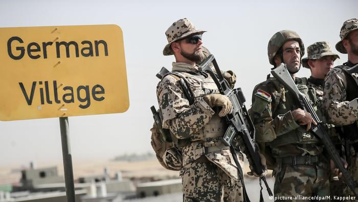German soldiers stand next to Peshmerga troops near a sign that says German Village (picture-alliance/dpa/M. Kappeler)