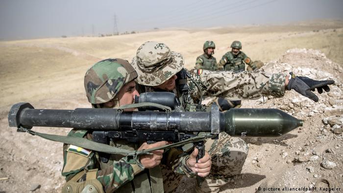 A Bundeswehr soldier and Kurdish Peshmerga troops in northern Iraq