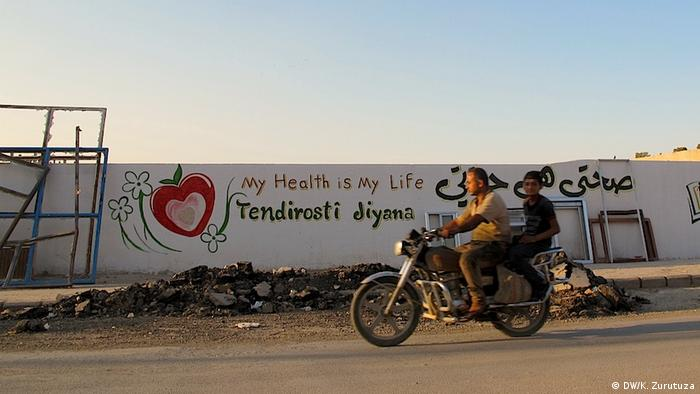 A man and boy on a motorcycle drive past a mural in Kobani