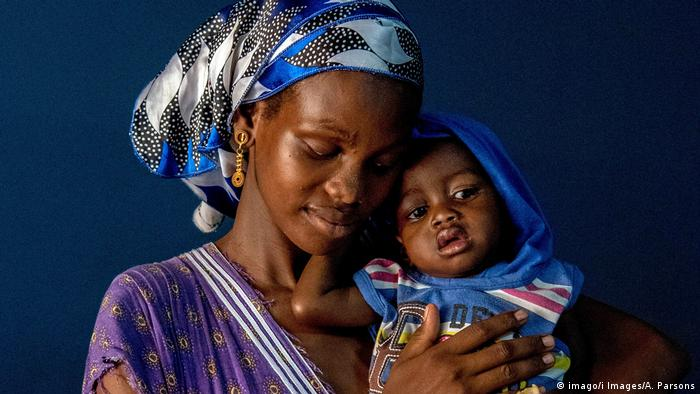 A woman in Senegal looks away from the camera as she hold her 16 month old son