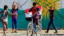 Irak Kirkuk - Junge fährt Fahrrad mit Irakischer Flagge