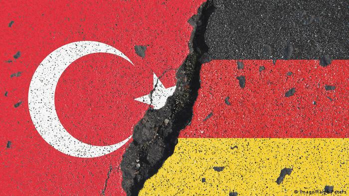Turkish and German flags painted on concrete with a crack between them