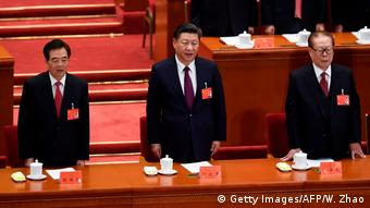 Chinas President Xi Jinping (C) sings the National Anthem with former presidents Jiang Zemin (R) and Hu Jintao (L)