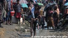 17.10.2017 TOPSHOT - A Rohingya refugee carries an old man in an area near no man's land on the Bangladesh side of the border with Myanmar after crossing the Naf River, after being told by border guards they were not allowed to leave the area and reach the refugee camps near Ukhia, on October 17, 2017. Some 582,000 Rohingya refugees have now fled Myanmar for Bangladesh since late August, the United Nations said October 17, warning that thousands more were still stranded at the border. / AFP PHOTO / MUNIR UZ ZAMAN (Photo credit should read MUNIR UZ ZAMAN/AFP/Getty Images)